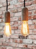 Simple pendant lamps with exposed light bulbs and concrete sockets