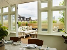 Set table in conservatory with view of white, nostalgic bench on roof terrace