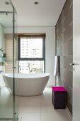 Purple bin lid as splash of colour in elegant, modern white bathroom with free-standing bathtub and dynamic pattern on wall