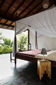 Wooden bed with mosquito-net canopy below open wooden ceiling in tropical surroundings
