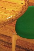 Detail of figured wooden table top and partially visible chair with green seat cushion