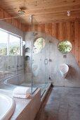 Corner of designer bathroom with glass shower screen and concrete walls panels merging into floor