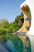 Unusual wooden house with apertures in protruding front facade, infinity pool and wild garden