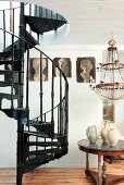 Black, metal, vintage spiral staircase next to various ceramic vases on table below chandelier