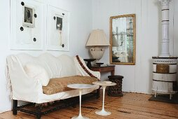 White plastic side tables in front of antique bench with ecru loose cover and white, vintage wood-burning stove