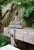 Metal statue of Buddha on vintage workbench in garden against wooden fence