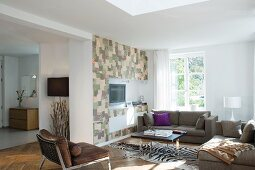 Modern seating area with zebra-skin rug and media cabinet with patchwork fronts in open-plan interior