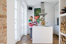 Woman and child in small, white designer kitchen with central island counter