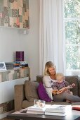 Mother and toddler reading on a sofa; wall of fitted cupboards to one side with patchwork-patterned fronts