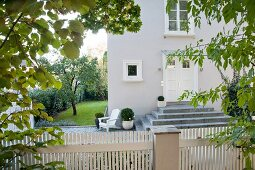 View over white picket fence of front door of house with stone steps and well-tended garden