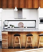 Retro bar stools at counter with rustic wooden front in modern fitted kitchen