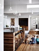 Two children playing with dog on wooden floor next to island counter below pendant lamps in open-plan kitchen