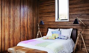 Simple double bed flanked by standard lamps with adjustable wooden bases in bedroom with dark wooden walls