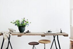 Bouquet (Nigella) in black ceramic vase on rustic wooden tabletop on metal trestles, partially visible vintage swivel stools under table