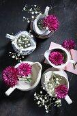 Lila Chrisanthemenblüten und Schleierkraut in Kännchen