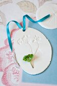 Pendant with impression of lady's mantle flower in plaster with blue ribbon