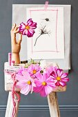 Small still-life arrangement of various cosmos flowers, pastel chalks and wooden jointed hand with floral drawing on grey wall in background