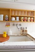 Glasses and painted crockery on wall-mounted wooden shelves above sink and white worksurface with peeling paint