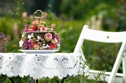 Romantic cake stand decorated with roses and other flowers on white broderie anglaise table cloth in summery garden