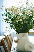 Bouquet of chamomile in white, nostalgic milk can on dining table