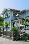 Restored country-house cafe with pale blue wooden facade, idyllic front garden and shady terrace