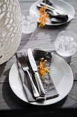 Two place settings with cutlery and yellow flowers on grey linen napkins