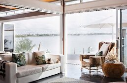 White leather couch and wicker armchair in open-plan interior with sea view
