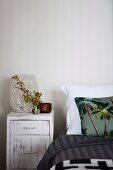 White shabby-chic bedside cabinet and scatter cushion with palm-tree motif on bed