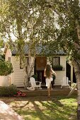 White clapboard play house with girl jumping up onto front wooden deck encircling silver birch tree
