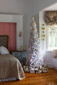 White and gold romantic Christmas tree and wrapped presents in faux-antique girl's bedroom
