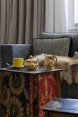 Gilt porcelain milk jug and sugar bowl on side table made from interlocking panels with floral, Art-Nouveau patterns in front of fur blanket on sofa