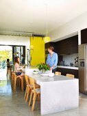Kitchen counter and adjoining, lower dining table made of marble slabs and Finnish classic chairs in open-plan kitchen