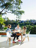 Family sitting on classic chairs at designer table on sunny terrace