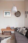 Designer ceiling lamp in corner above grey sofa and vintage suitcase below side table