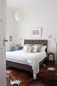 View of double bed with upholstered headboard and silver-grey scatter cushions in bedroom