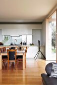 Dining area in front of white fitted kitchen with same-level access to terrace