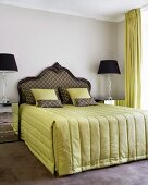Antique-style double bed with curved headboard flanked by elegant, modern bedside lamps on mirrored cabinets