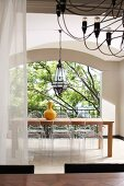 View across dining table below black chandelier to dining area with postmodern plexiglass chairs in roofed courtyard