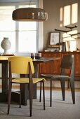 Modern dining table and chairs below glossy pendant lamp in sunny dining room with grey walls