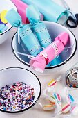 Pastel crackers decorated with washi tape and confetti in enamel bowls