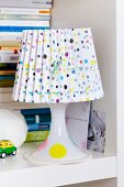 Table lamp with confetti-patterned lampshade on bookshelf