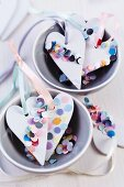 Heart-shaped pendants decorated with confetti in china bowl