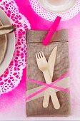 Leinenserviette und Holzbesteck auf pink auf pink gespraytem Tortenspitzen als Platzset