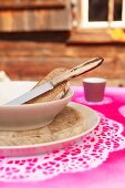 Gedeck mit Suppenschale auf gespraytem Tortenspitzen als Platzset vor Almhütte