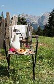 Brotzeit auf Vintage-Holzstuhl in sommerlicher Wiese, im Hintergrund Berglandschaft