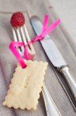 Keks mit pinkfarbenem Band als Platzkarte an Silberbesteck mit Himbeere dekoriert