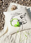 Trendy headphones in neon green on cushion and woollen blanket on gravel floor