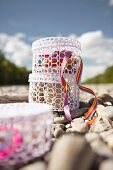 Haberdashery supplies in two, stacked, white crocheted containers on pebbly river bank