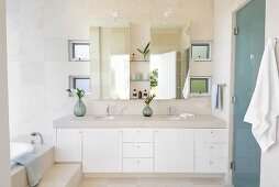 Washstand with stone top, twin countertop basins and white cabinets below mirrored cabinet in bright, modern bathroom