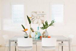 Various vases of bird-of-paradise flowers and palm fronds on grey table, white chairs and interior shutters on windows